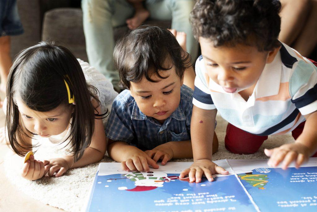 Kinderen spelen op de vloer met een boek